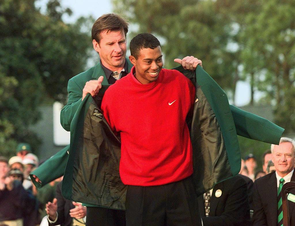Tiger Woods (R) Receives The Masters Green Jacket